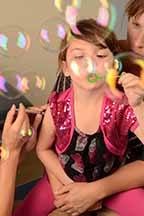 Child blowing bubbles while being vaccinated