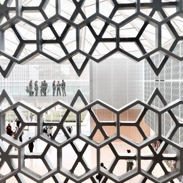 A photo of people standing behind a metal see-through wall of varying shapes.