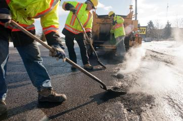 Road workers filling in a pot hole on the street
