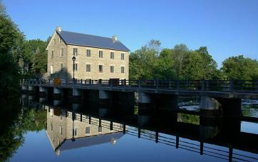 Exterior image of Watsons Mill and its reflection in the water.